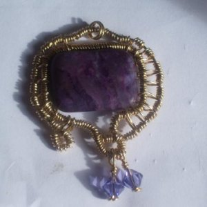 This is a brass square-wire handmade form wrapped with 14kt gold filled wire with an amethyst coloured stone and 2 Swarovski dangles.  This was donated to my little girls school fayre for their raffle.
