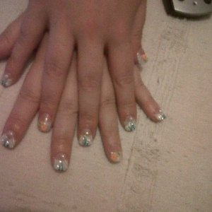 Acrylics with white tips and faded blue glitter acrylic blue and white flicks with pearl and rhinestones on 3 fingers Thumb and ring finger have multi fimo slices