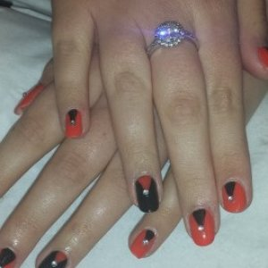 Orange and black nail art with gems.
