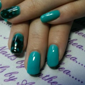 Turquoise teacup with guinea foul feather nail art